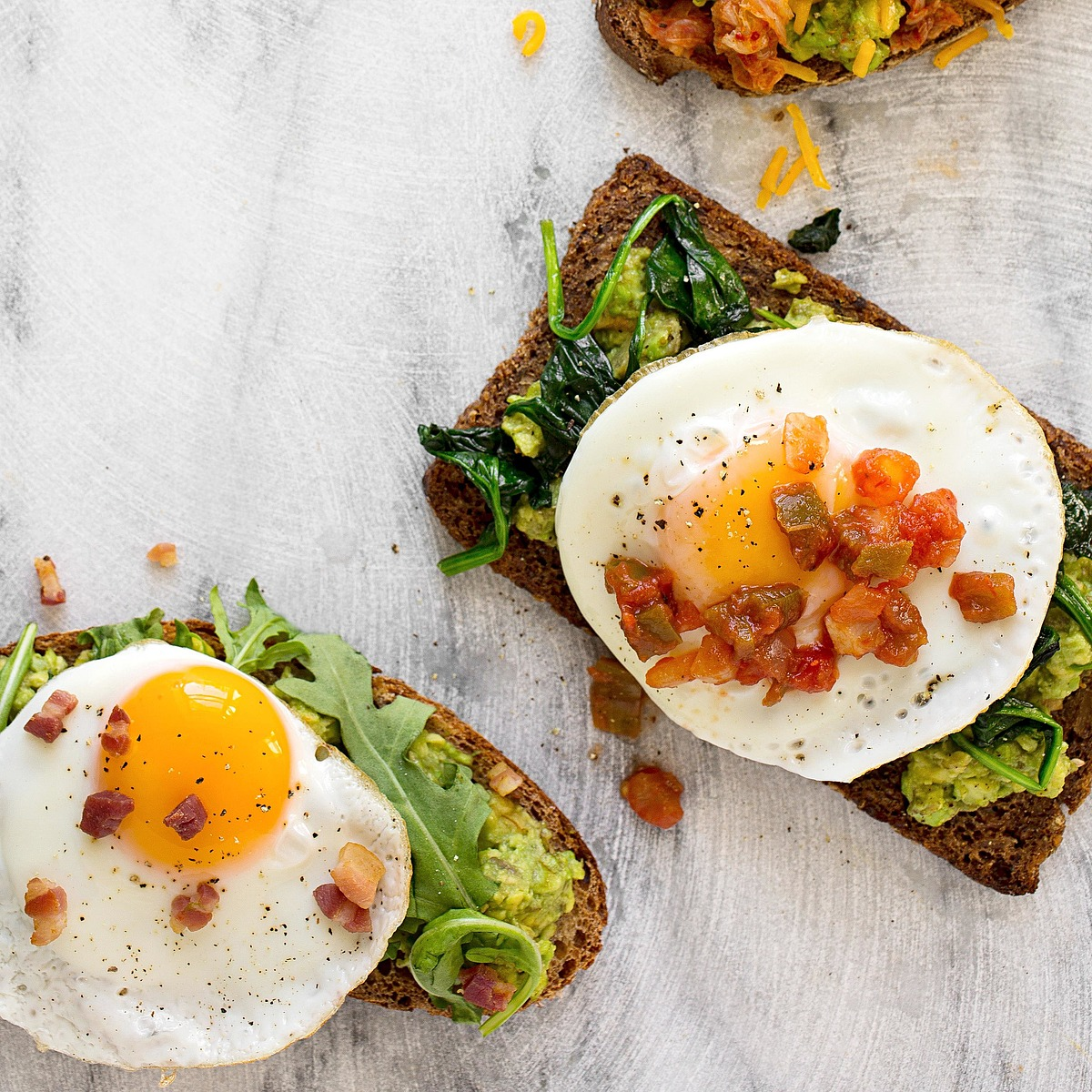 avocado toast with egg, arugula, and bacon